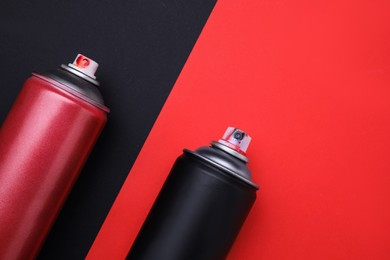 Cans of different graffiti spray paints on color background, flat lay
