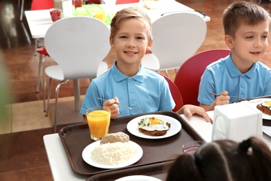 Cute children at table with healthy food in school canteen