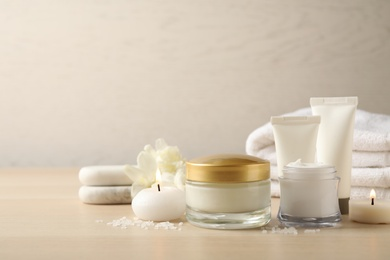 Spa composition with skin care products and candles on wooden table. Space for text