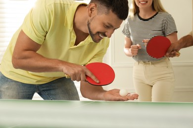 Happy man playing ping pong with friends indoors