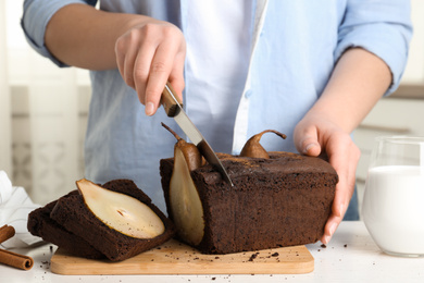 Woman cutting tasty pear bread at table, closeup. Homemade cake