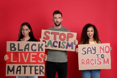 Protesters demonstrating different anti racism slogans on red background. People holding signs with phrases
