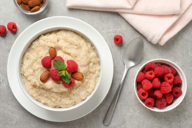 Tasty oatmeal porridge with raspberries and almond nuts served on light grey table, flat lay