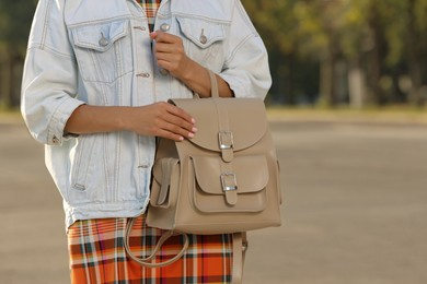 Young woman with stylish beige backpack on city street, closeup