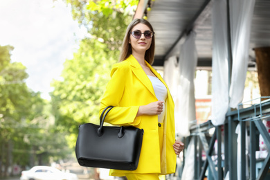 Beautiful young woman with stylish leather bag outdoors on summer day
