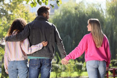 Man holding hands with another woman while hugging his girlfriend during walk in park, back view. Love triangle