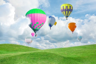 Fantastic dreams. Hot air balloons in sky with fluffy clouds over green meadow