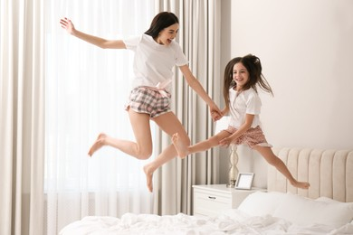 Young mother and her daughter jumping on bed at home