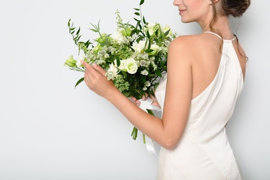Young bride wearing wedding dress with beautiful bouquet on light grey background, closeup