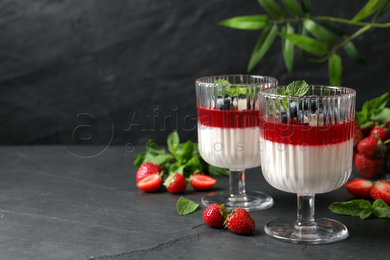 Delicious panna cotta with fruit coulis and fresh berries on dark grey table. Space for text