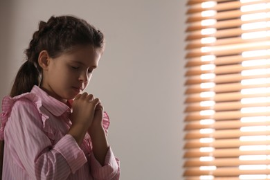 Cute little girl with hands clasped together praying near window. Space for text