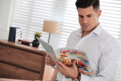 Man reading new culinary magazine in room