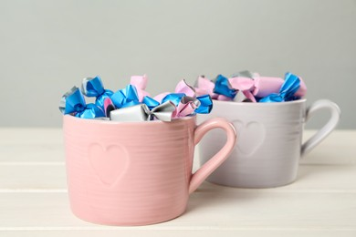 Candies in colorful wrappers on white wooden table