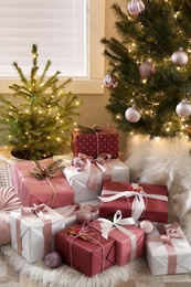 Gift boxes under small and big Christmas trees indoors