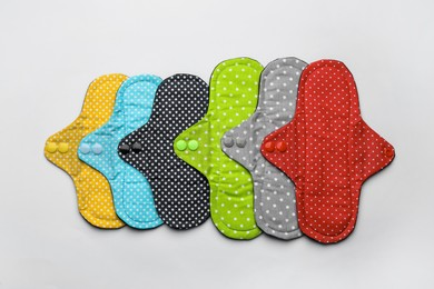 Many reusable cloth menstrual pads on white background, flat lay