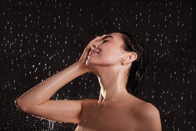 Young woman washing hair while taking shower on black background