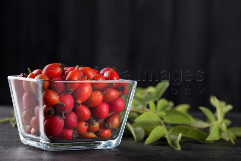Ripe rose hip berries with green leaves on black table. Space for text