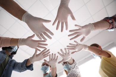 People in white medical gloves joining hands on light background, low angle view