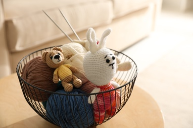 Basket with set of color threads and knitted toys on table indoors. Handicraft as hobby