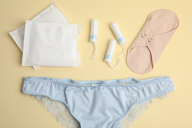 Tampons and other menstrual hygienic products on yellow background, flat lay