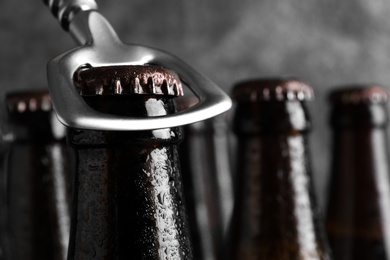 Opening bottle of tasty cold beer on grey background, closeup. Space for text