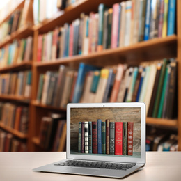 Digital library concept. Modern laptop on table indoors