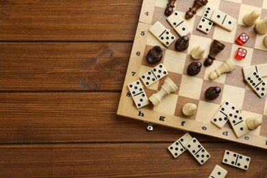 Elements of different board games on wooden table, flat lay. Space for text