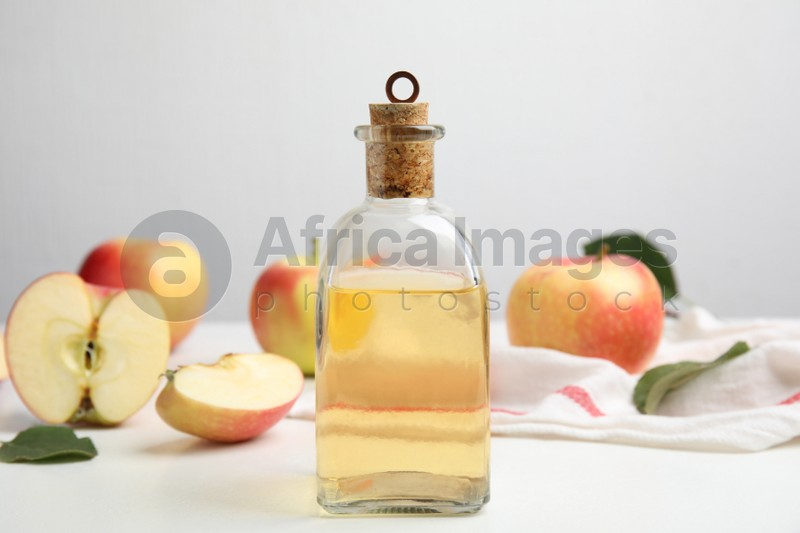 Natural apple vinegar and fresh fruits on white table
