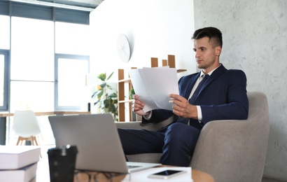 Male business trainer working with documents in office