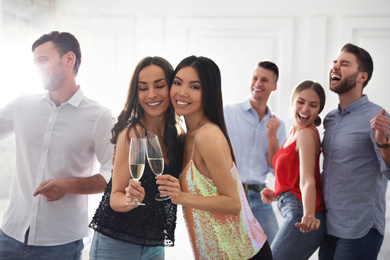 Couple of happy friends with champagne dancing at party