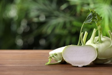 Whole and cut kohlrabi plants on wooden table. Space for text