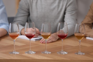 Different sorts of wine in glasses prepared for tasting and sommeliers at wooden table indoors, closeup