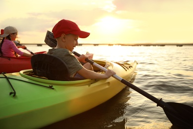 Happy children kayaking on river at sunset. Summer camp activity