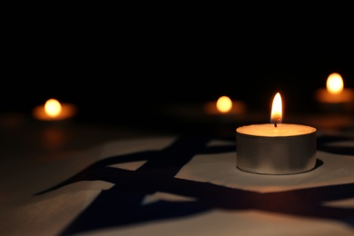Burning candle on flag of Israel. Holocaust memory day