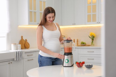 Young pregnant woman preparing smoothie at table in kitchen. Healthy eating