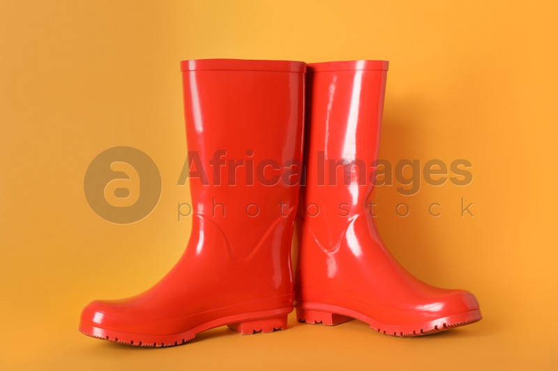 Pair of red rubber boots on orange background
