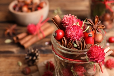 Aromatic potpourri in glass jar on table, closeup. Space for text
