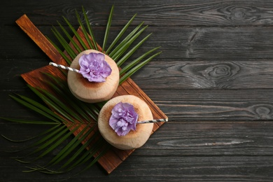 Fresh coconuts with drinking straws on black wooden table, top view. Space for text