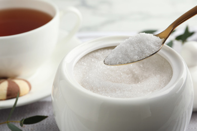 Spoon with granulated sugar over bowl on table, closeup