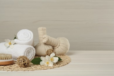 Composition with beautiful jasmine flowers, towels and herbal bags on white wooden table, space for text