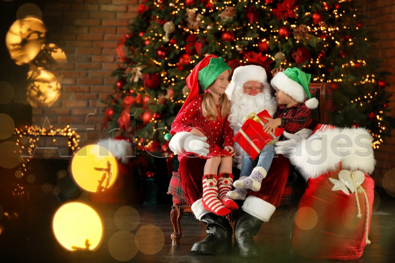 Santa Claus and little children with present near Christmas tree indoors