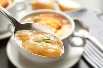 Spoon with fresh homemade homemade french onion soup over bowl, closeup
