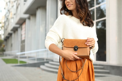 Young woman with stylish brown bag on city street, closeup