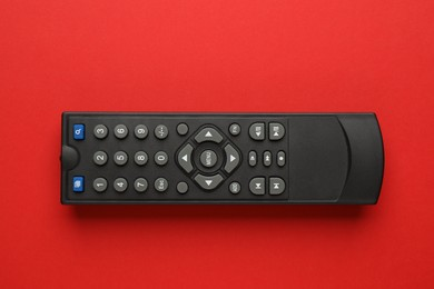 Remote control on red background, top view