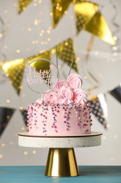 Beautifully decorated birthday cake and party decor on turquoise wooden table against blurred festive lights