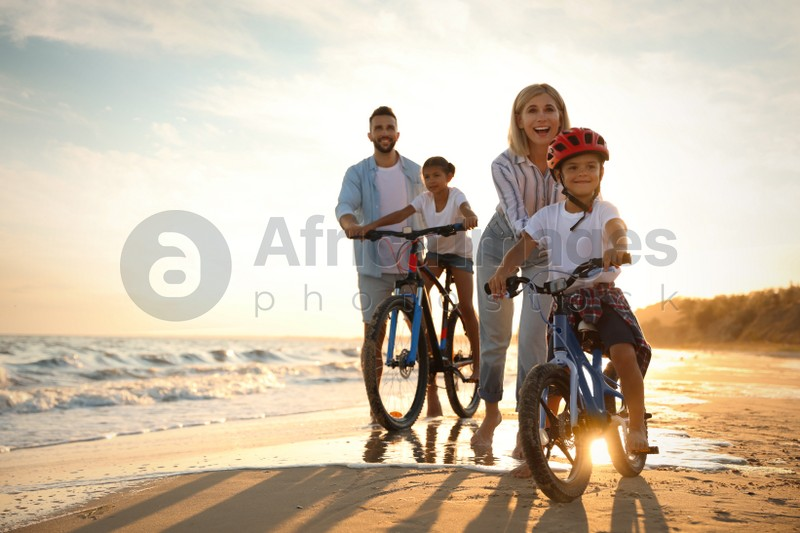 Happy parents teaching children to ride bicycles on sandy beach near sea at sunset