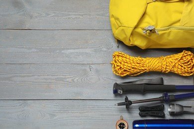 Flat lay composition with trekking poles and other hiking equipment on wooden background, space for text