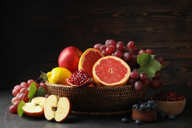 Wicker basket with different fruits and berries on black table
