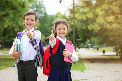 Cute little school children with stationery in park