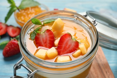 Delicious panna cotta with mango coulis and fresh fruit pieces on light blue table, closeup